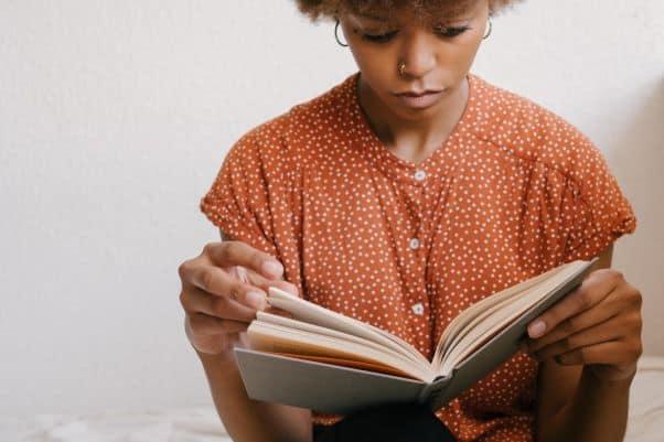 Woman sits on bed and reads Swahili hardback novel.