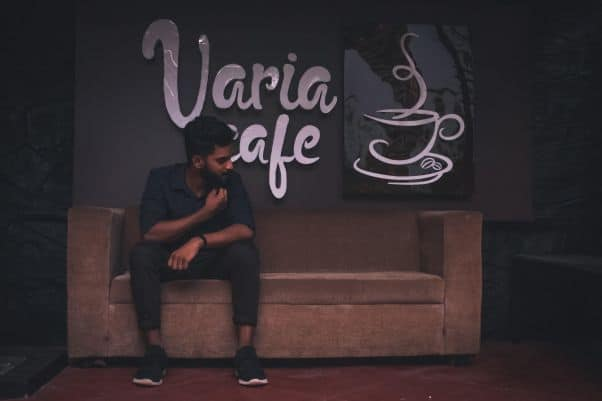 A man sits in front of a Varia café sign