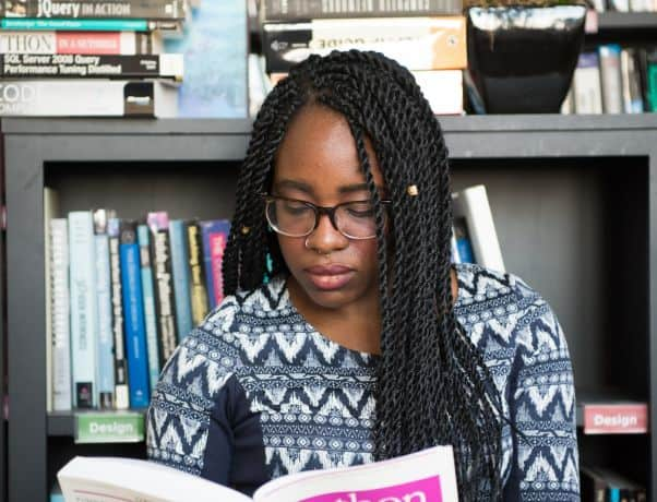 A young woman reads a Swahili textbook in front of a bookshelf.