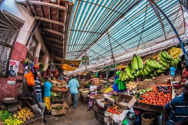 A covered market in Kenya with fruit and vegetable stalls