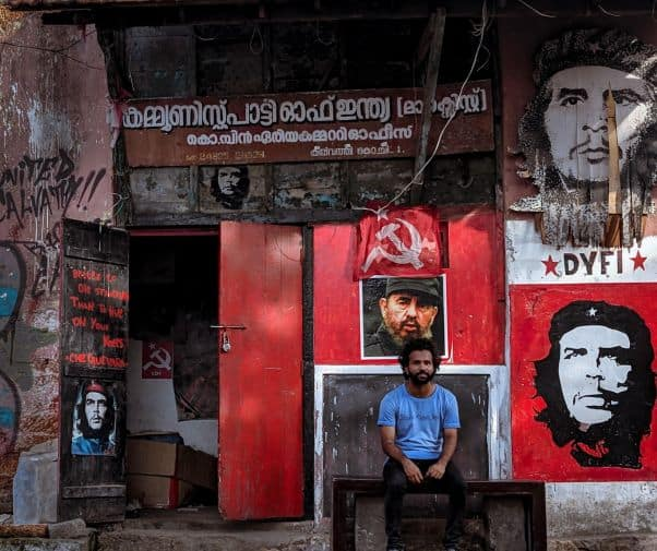 A man sits outside a building with communist motifs and writing in English and Malayalam, flags, and images of Che Guevara