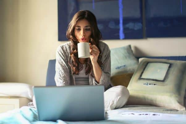 Young woman sits on bed, drinks coffee, and watches a Swahili movie.