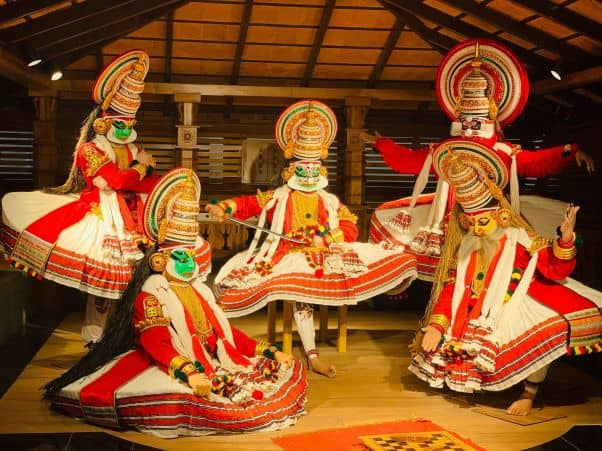 Five masked actors perform Kathakali on a stage that looks like a house