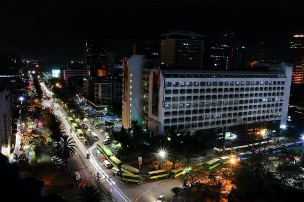 A brightly lit street lined with dark buildings in Nairobi