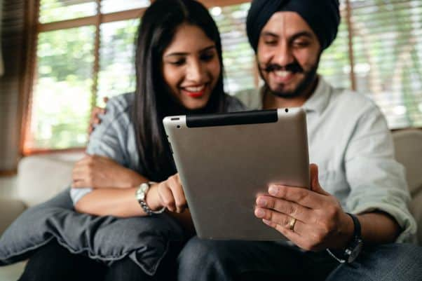 South Asian couple watch Swahili YouTube videos on a tablet.