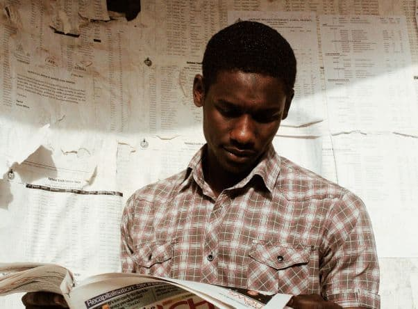Young man reads a Swahili-language newspaper