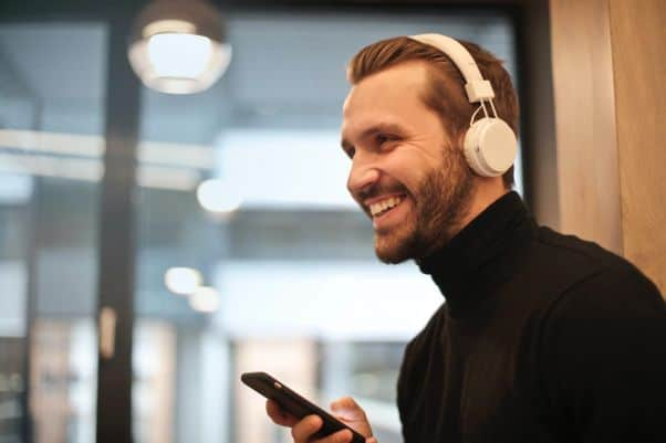 Young man smiles while listening to a Swahili-language podcast in the office.