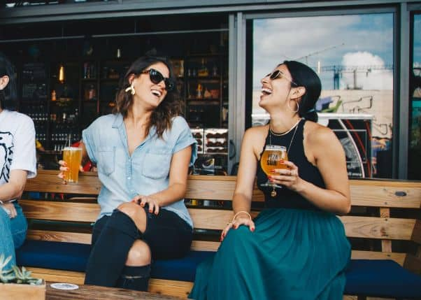 Two girls in a bar laugh and talk in Swahili.