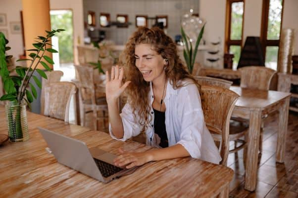 A smiling woman smiles and waves during an online language class