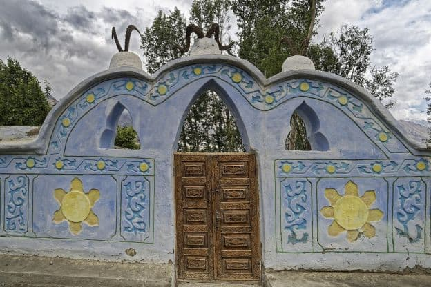 A decorated blue stone wall in Vrang, Tajikistan. There is a set of wooden doors in the middle of the wall, surrounded by arches and carvings that look like flowers or suns. Three sets of antlers or horns top the wall.