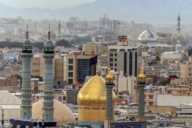 A view of mosques and other buildings featuring onion domes and minarets in the city of Qom, Iran.