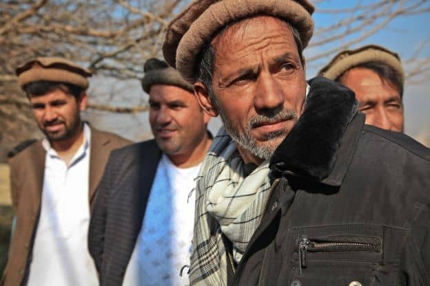 A small group of Afghan men stand in the autumn sun, each wearing a traditional wool cap known as the pakol.