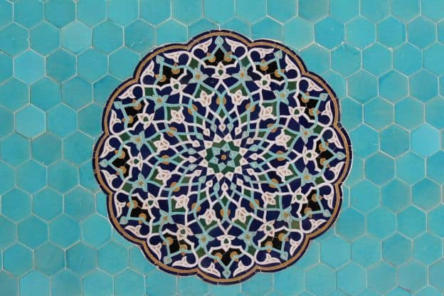 A mosaic of an intricate geometric pattern on a background of light blue tiles; part of the design of a mosque in Ishafan, Iran. The pattern is reminiscent of a rose window.