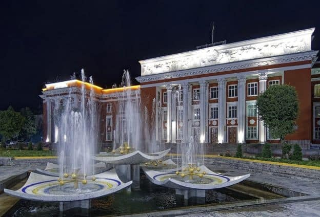 Three water fountains run at night in front of the Houses of Parliament in Dushanbe, Tajikistan's capital. The Parliament building, with neoclassical architecture, is painted a reddish color.
