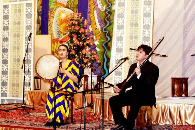 A female and a male folk performer sit next to each other on a colorful stage. The woman is holding what appears to be a drum, and the man has a stringed instrument.