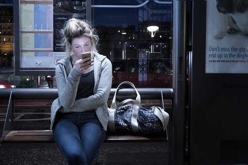 An image of a woman using her smartphone on public transportation at night. Mobile apps let you take advantage of bits of idle time to study Persian.