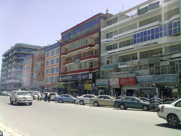 Part of a city block in a commercial district in Kabul, Afghanistan. There are shops in large buildings, with several cars parked out front and shoppers walking down the street.