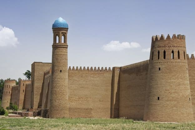 The fortress-like exterior of a citadel in Hulbuk, Tajikistan, features characteristics of Persian architecture, such as a domed minaret.