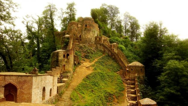 The image shows the steep steps to the ruins of Rudkan Castle in Gilan Province. The stone ruins are overgrown with greenery.