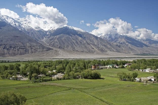 Flat, green fields with trees and houses are in the foreground of mountains that reach the clouds in the Badakhshan region of Tajikistan.
