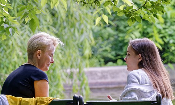 A close-up image of two friends chatting outdoors, practicing their Persian together.