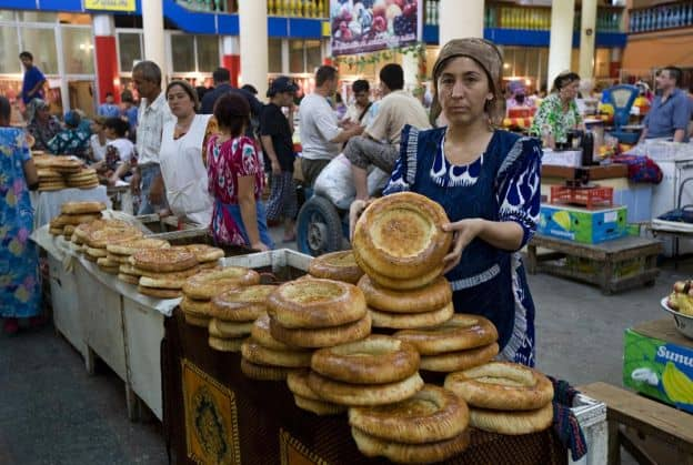A Tajik woman holds up a round loaf of bread. She is standing in front of a table filled with multiple loaves of similar bread at a marketplace. There are many other people in the background.