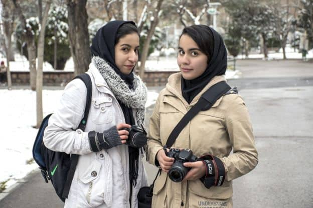 Two young women stand next to each other in snow-covered Mellat Park in Mashhad, Iran. The women are wearing winter coats and dark hijabs, and each is carrying a camera.