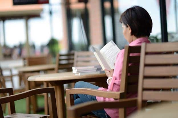 Image of a seated woman reading casually at a round table, probably in a café or cafeteria. There are a few books stacked on the table in front of her.