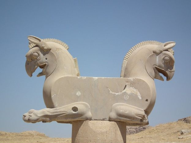 An ancient statue at Persepolis appears to be a double-headed horse, with matching manes and beak-like face, against a desert backdrop.