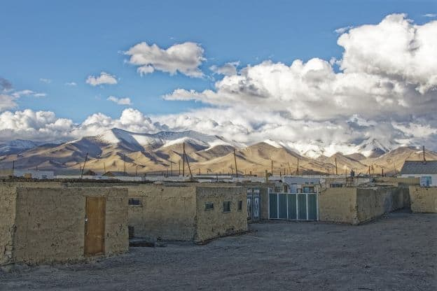 One-storey houses with flat rooves sit at the base of mountains in Karakul, Tajikistan.