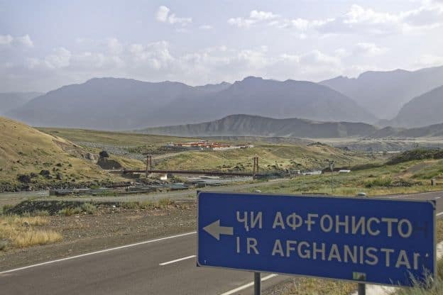 Road sign in Tajiki, with secondary text in the Latin alphabet, indicating the border between Tajikistan and Afghanistan. The Friendship Bridge over the Panj River is shown in the background.