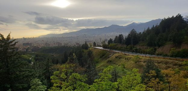 A panoramic landscape of mountains and trees, with a road winding through, on an overcast day. The city of Tehran, Iran, can be seen in the background.