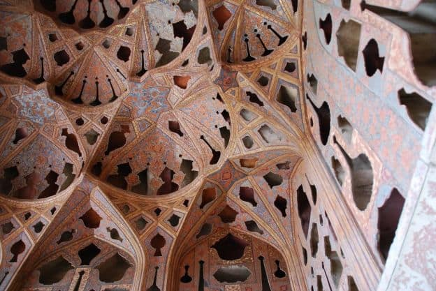 A view upward to the elaborate ceiling of the Music Hall at the Ālī Qāpū Palace at Isfahran, Iran. The intricate designs, with archways in numerous geometric shapes, are painted in detailed designs.