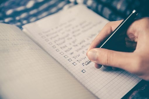 Image of someone writing a checklist in a journal, as one might use to track goals for learning Persian.