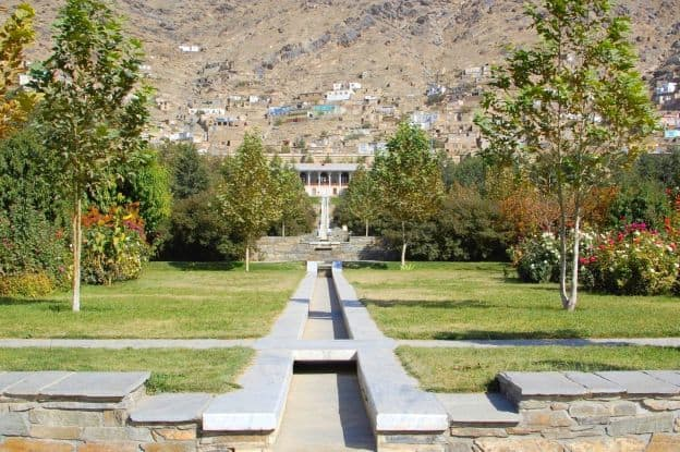 Neatly trimmed grass and other greenery, as well as flowers, are part of the Gardens of Babur in Kabul. Visible in the background are light brown houses built into the mountains.