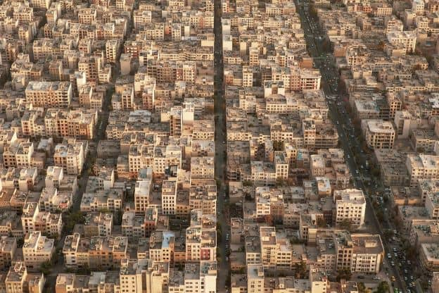 A view from above of a residential area in Tehran, Iran. The houses have largely streamlined rectangular architecture, and are densely packed together.