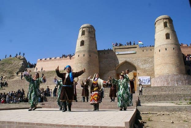 A group of folk performers in traditional Tajik costumes performs outdoors at Hissar Fortress, an ancient building with high walls and towers. There appear to be both dancers and musicians in the group.