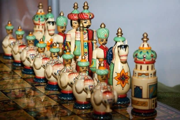 Colorful, carved chess figures in Persian garb stand guard on a reflective chess board.