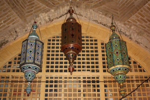 Three ornate lamps hang from a brick ceiling in front of a wooden screen at a mosque in Isfahan, Iran.
