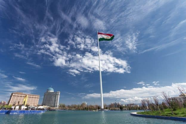 Two modern buildings rise up next to the river in Dushanbe, the capital of Tajikistan. A Tajik flag graces the center of the scene.