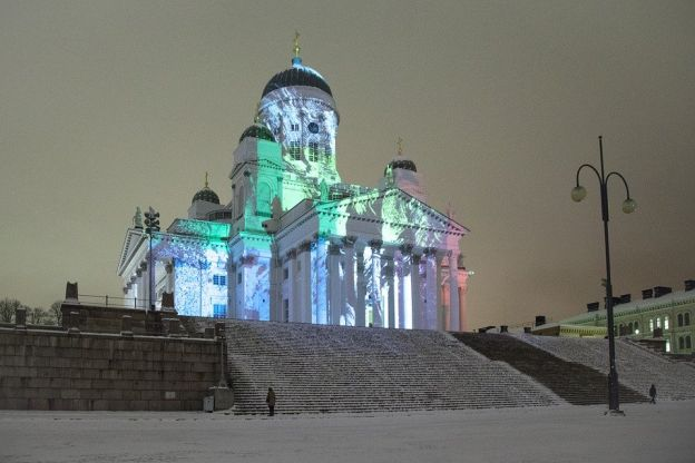 Against a stark background of a tawny-gray sky, the white façade of Helsinki Cathedral is vividly colored with pictures by a projected light show. The Cathedral looms above a steep double-flight of snowy stairs.