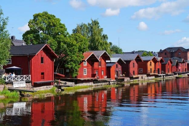 A row of red, wooden houses sits beside the water in Porvoo, Finland.