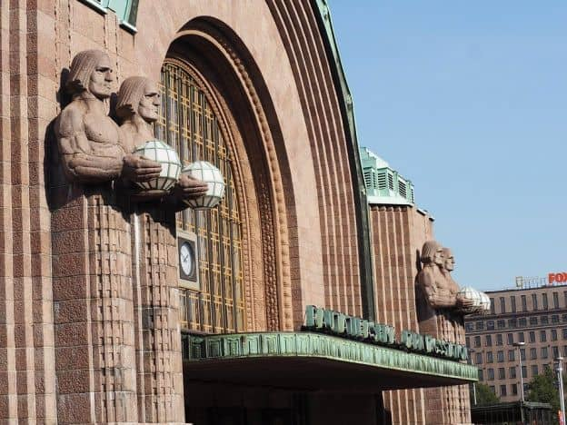 The art-deco Helsinki Central Railway Station is made of reddish-brown stone. Four large statues of men bearing globes of light flank the arched central entryway, from which projects an oxidized metal awning.