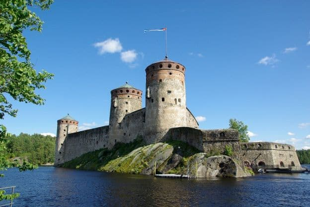 St. Olaf's Castle, with its round turrets and high walls, rises above the water on a clear, sunny day in Savonlinna, Finland.