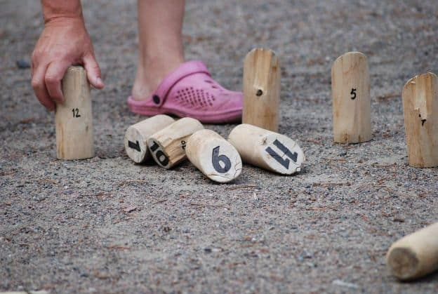 A close-up of a player of a Finnish/Karelian skittles game, this image shows numbered wooden stakes planted in sandy soil