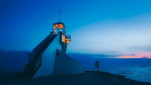 A modern-looking, white lighthouse on the edge of the water in Oulu, Finland graces the sky at sunset.