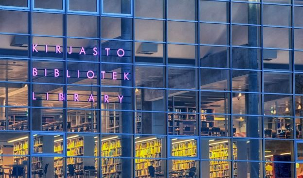 A view of the glass-covered walls of a city library in Oulu, Finland. Multiple stories of the library stacks are visible, as are some patrons. The library is identified by a purple neon sign in Finnish.