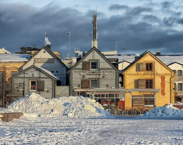 In this winter scene in Oulu, Finland, snow is piled high outside of shops in painted wooden buildings