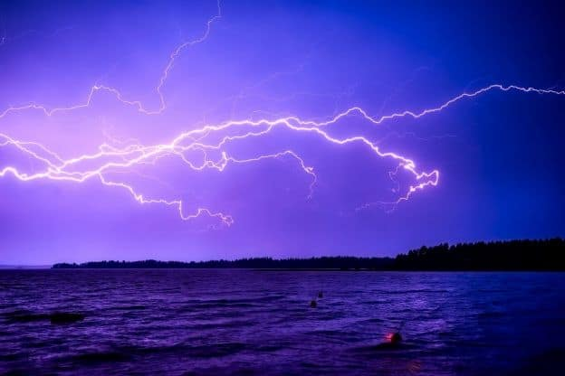 At dusk, lighting flashes through a purple-colored sky above a body of water in Finland.
