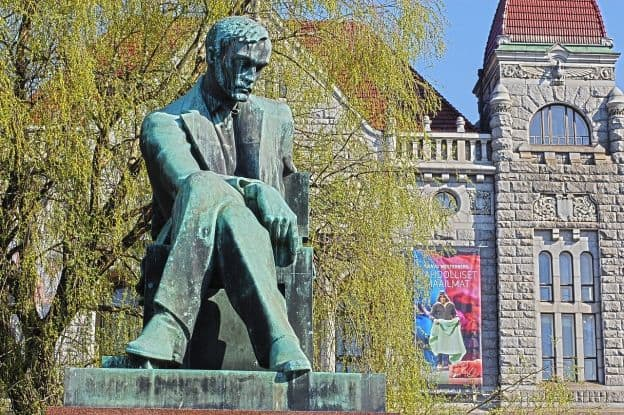 An oxidized bronze statue of author Aleksis Kivi in a contemplative pose. There is a tree and a stone railway building behind the statue.